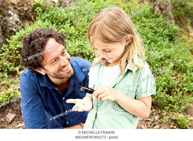 Girl with father looking through magnifying glass