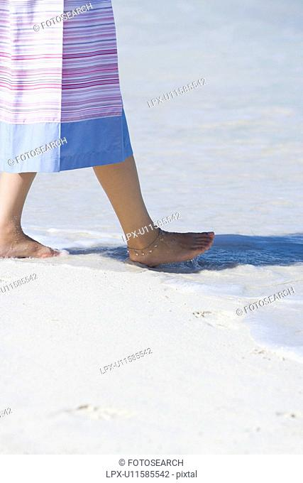 Young woman walking on beach, Saipan, USA