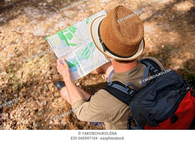 Young male tourist is looking for place of destination. He is sitting on ground in forest and holding map. Focus on his back