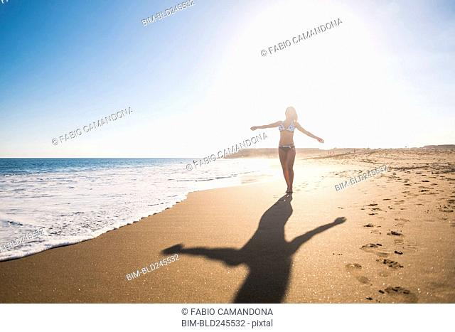 Carefree Caucasian woman walking on beach