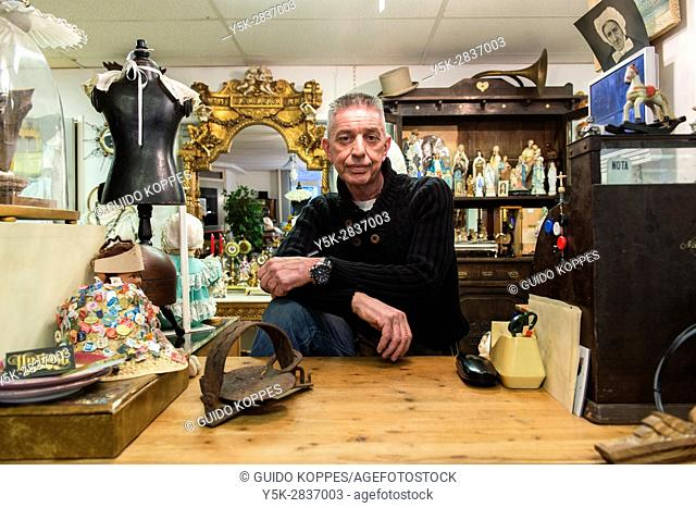 Tilburg, Netherlands. Mature adult vintage shop owner selling retro interior decoration items from his down town store