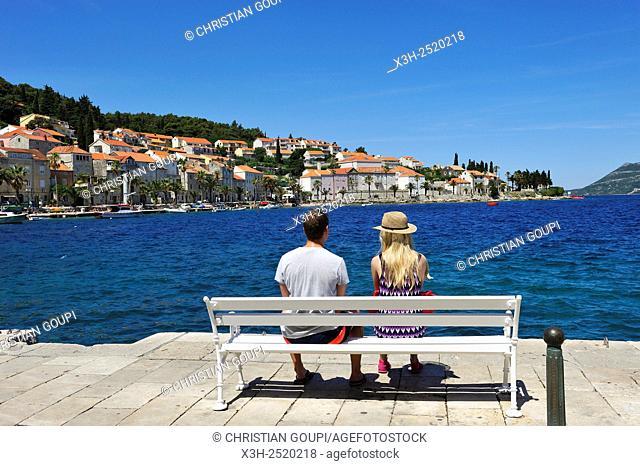 young couple sitting on a bench on the promenade Obala Franje Tudmana, Korcula old town, Korcula island, Croatia, Southeast Europe