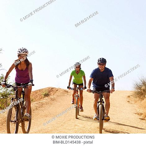 Friends riding mountain bike on dirt road