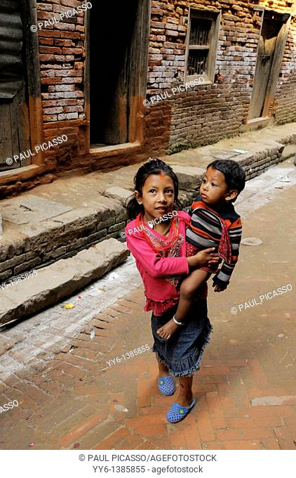 nepalis girl holding her brother , the nepalis , life in kathmandu , kathmandu street life , nepal