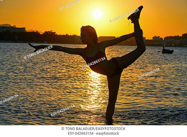 Girl gymnastics pose at sunset beach in orange sky
