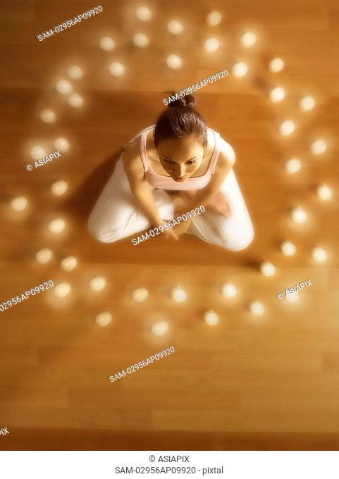 girl meditating surrounded by candles
