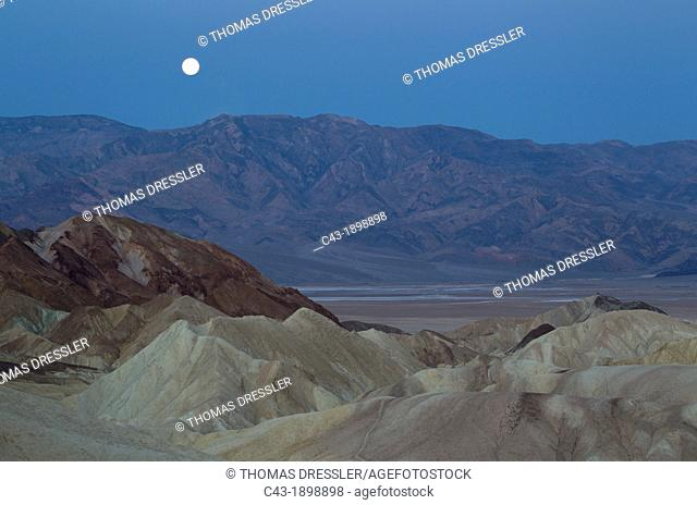Full moon at dawn over the Panamint Range and the Death Valley  Seen from Zabriskie Point with the badlands of Gower Gulch in the foreground  Death Valley...