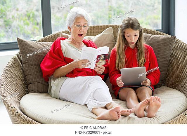 Senior woman and her granddaughter looking surprised