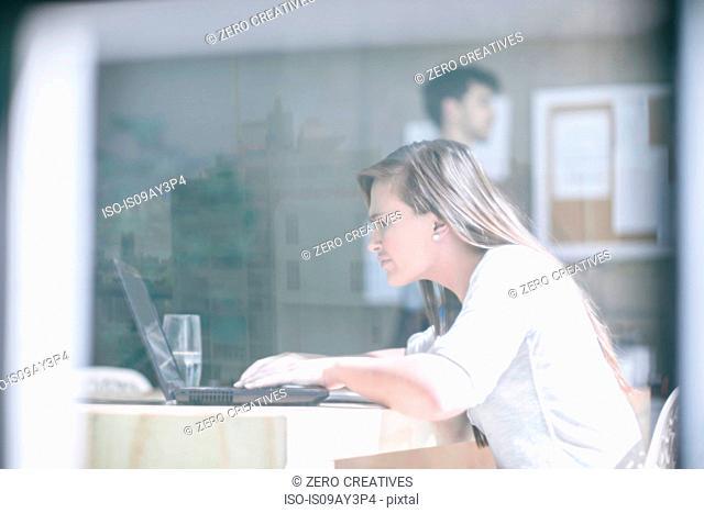 Window view of female designer working on laptop at design studio