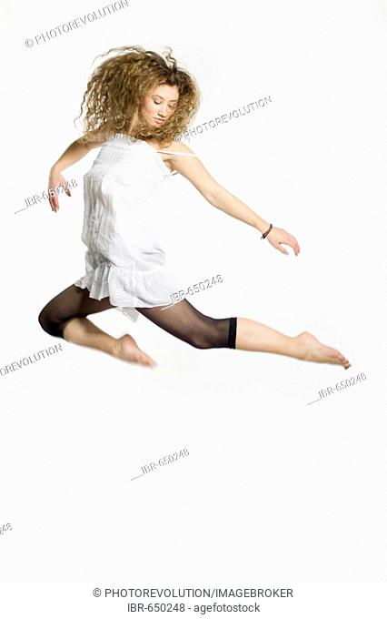 Young woman jumping in front of a white background