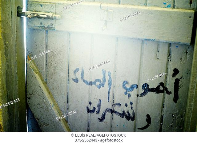 Wooden door of a toilette with a lock and handwritten text in Arabic. Fez, Morocco, Africa