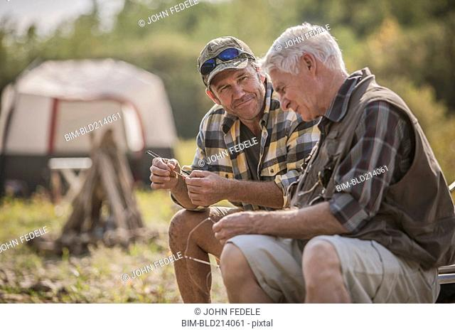 Caucasian father and son tying fishing lures at campsite