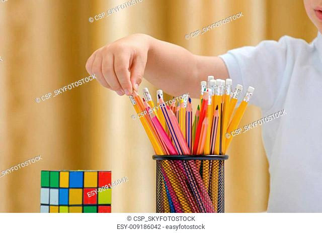 Beautiful child choose between more colored pencil