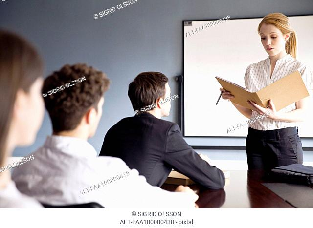Businesswoman presenting report at corporate meeting