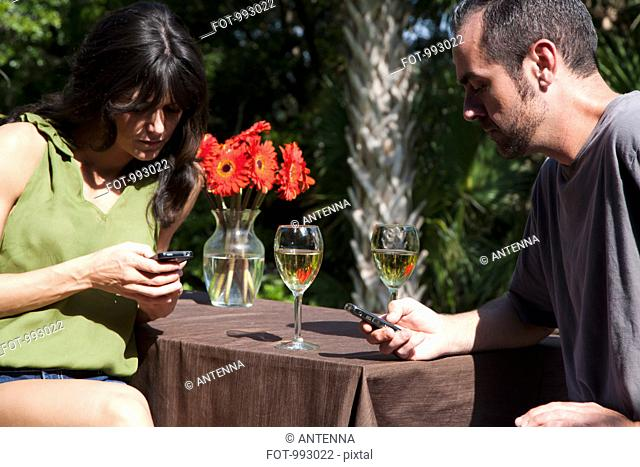 A man and woman text messaging on separate mobiles while on a backyard deck