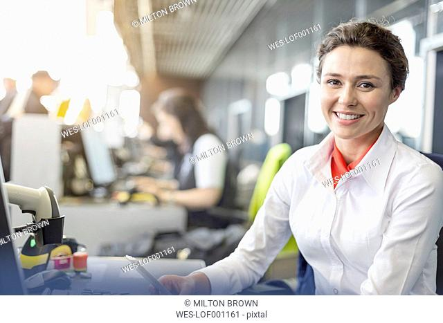 Portrait of smiling flight attendant at airport check-in