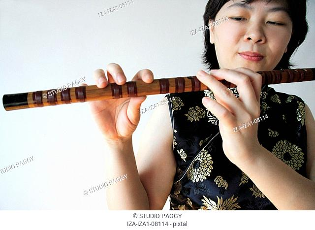 Close-up of a mid adult woman playing a flute