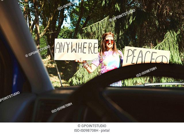 Car window view of young female boho hitchhiker with peace sign