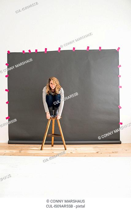 Mid adult woman crouching on top of stool