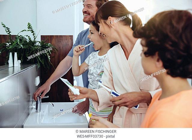 Family of four brushing their teeth in bathroom