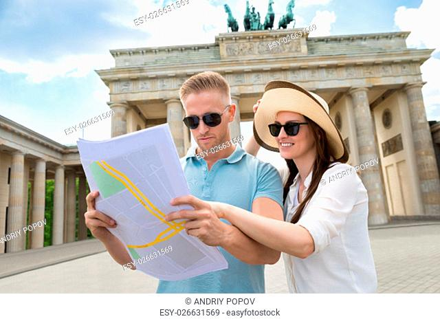 Young Couple Looking At Map In Front Of Brandenburg Gate