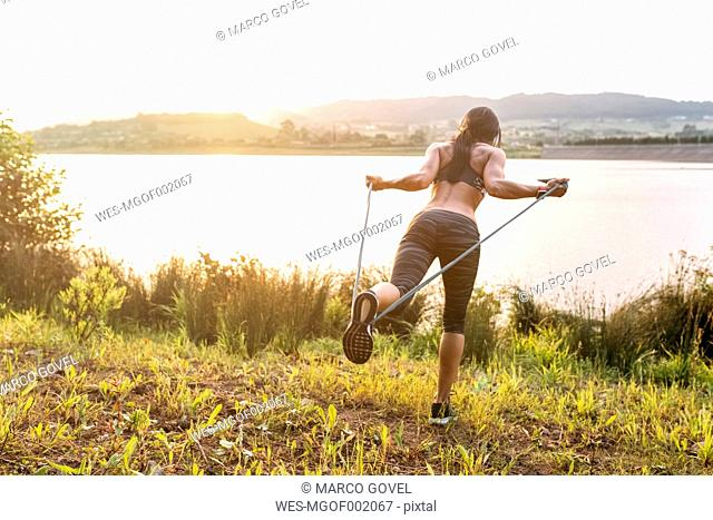 Woman doing resistance training outdoors at sunset