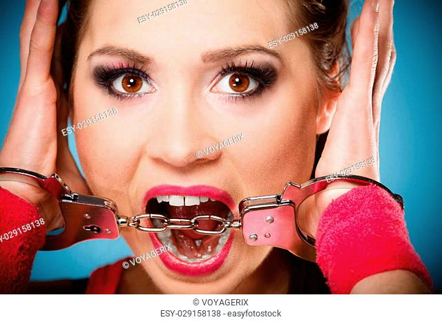 Teen crime, arrest and jail - Criminal teenager girl prisoner woman in handcuffs blue background