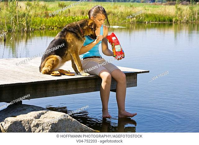 Teenaged girl and her pet dog eating potato chips outside at a lake