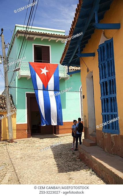 Young student couple in front of the colonial buildings at the town center with a huge Cuban flag at the background, Trinidad, Sancti Spiritu Province, Cuba