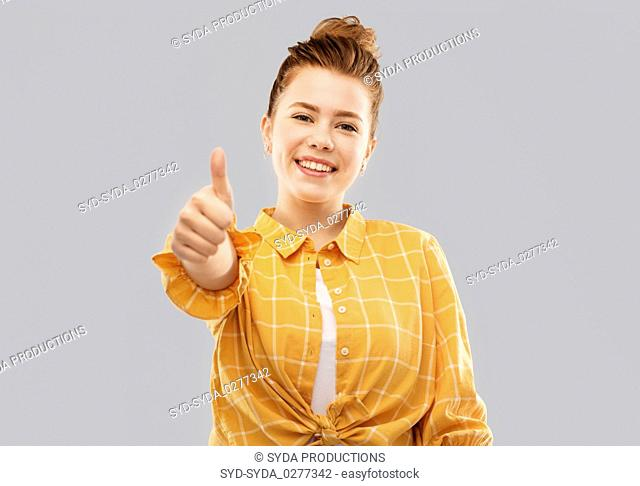 smiling red haired teenage girl showing thumbs up