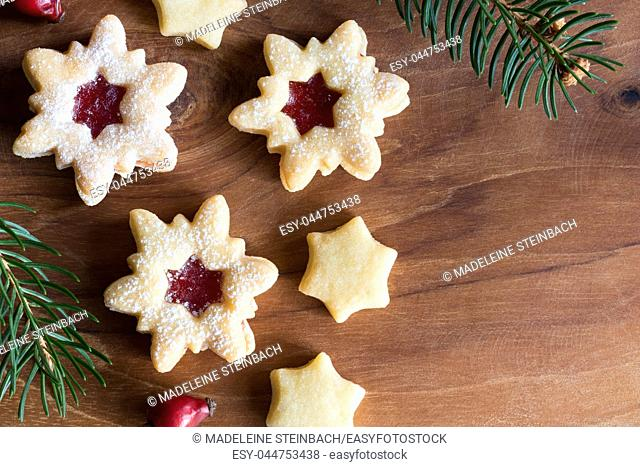 Christmas background with star-shaped Linzer Christmas cookies with strawberry jam, dried rose hips and spruce branches