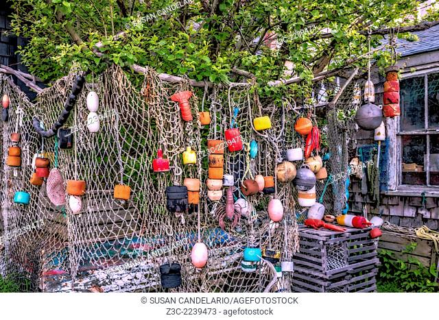 Fishing net and buoys adorn the outside of a fishing hut at Bradley Wharf in Rockport, Massachusetts