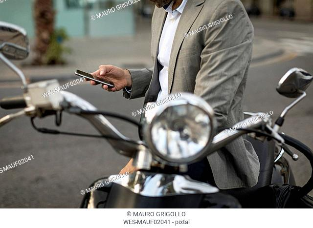 Close-up of businessman on motorscooter checking cell phone