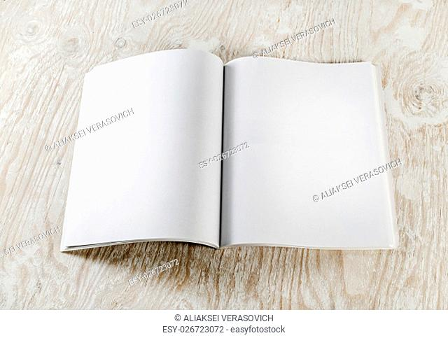 Blank opened book with soft shadows on light wooden background. Responsive design template. Mock-up for your design. Top view