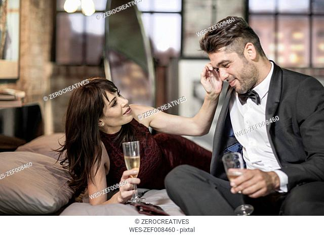 Smiling couple in elegant clothing drinking champagne in bed