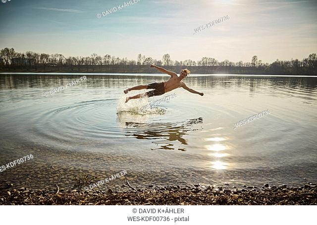 Germany, Bavaria, Feldkirchen, man jumping in lake
