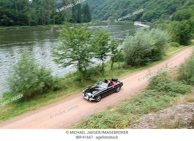 Black vintage car MG with red seat covers driving along a river