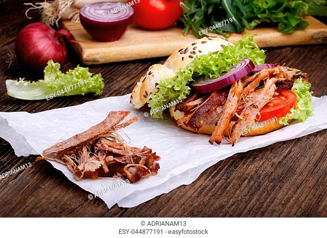 Pulled pork burger with coleslaw tomato, onion and fresh bread. Meat burger