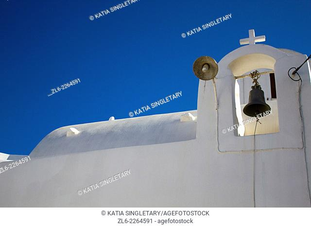 White orthodox church with cross on the top and a bell hanging, against deep blue sky. Pyrgos was built on the top of a hill and was until the early 1800