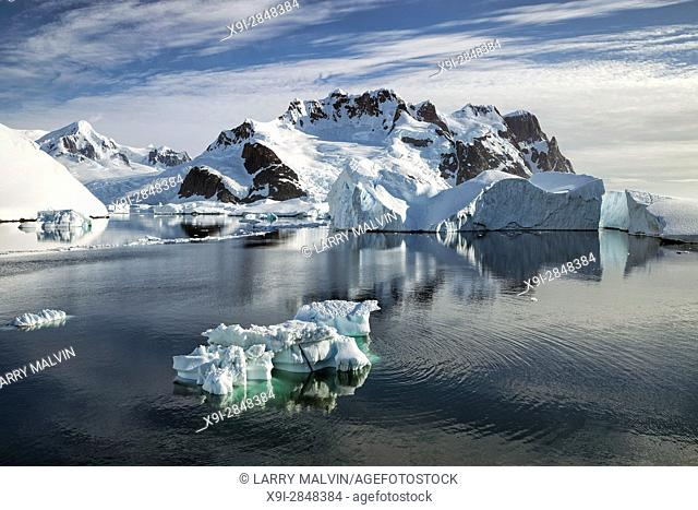 Iceberg in the waters of the Lemaire Channel with mountains and glaciers along the Antarctic Peninsula