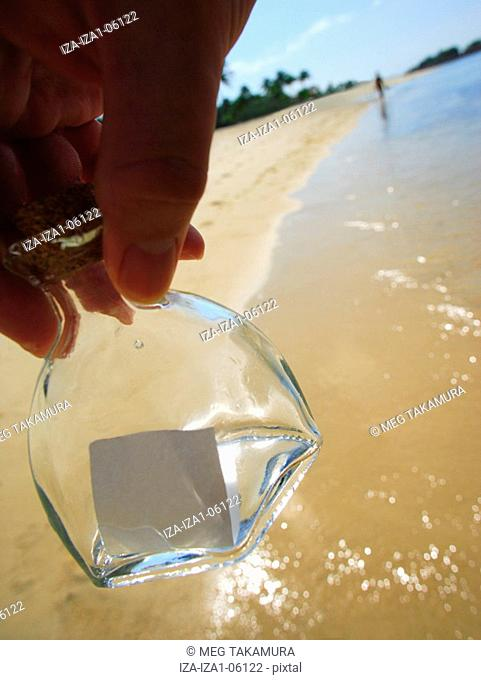 Close-up of a person's hand holding a message in bottle on the beach