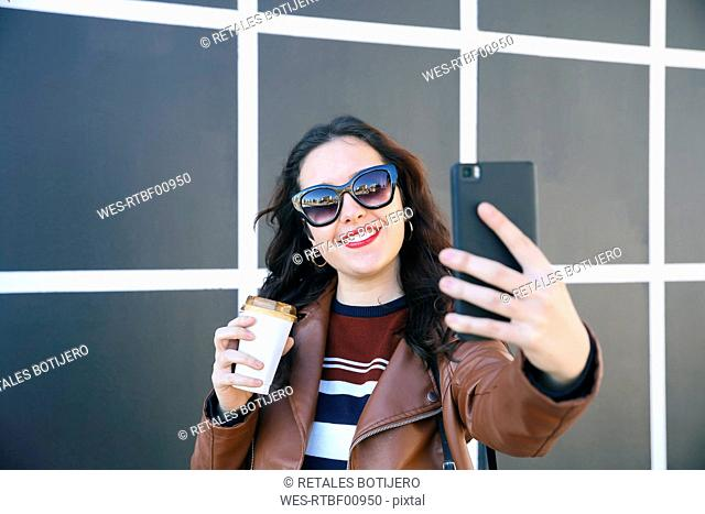 Portrait of smiling young woman with coffee to go taking selfie with smartphone