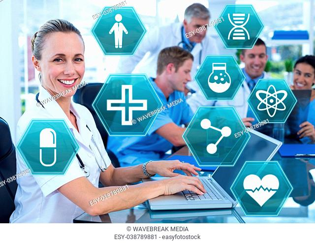 Female doctor working on laptop with medical interface hexagon icons