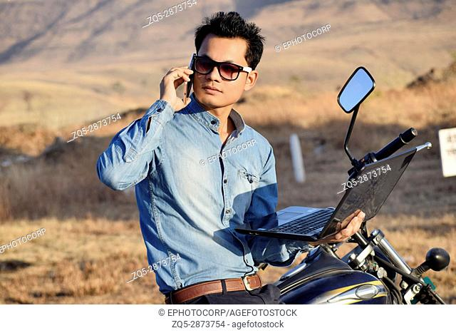 Young man talking on cellphone near mountain, Pune, Maharashtra