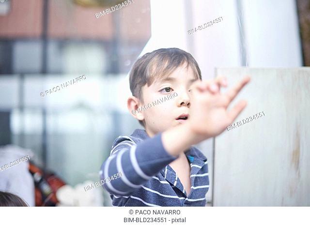 Hispanic boy touching window