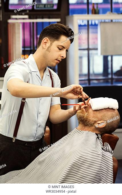 A customer sitting in the barber's chair, with a hot towel on his face, and a barber trimming his beard