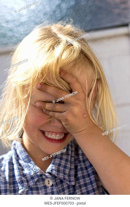 Blond little girl covering eyes with her hand