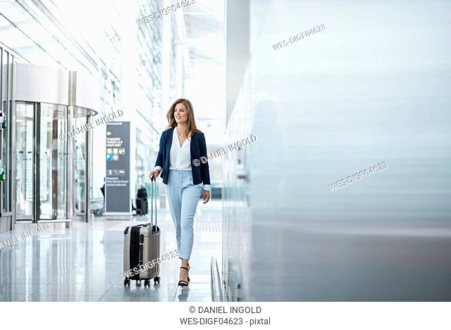 Young businesswoman walking with luggage at the airport