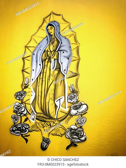 A mural shows a silvery image of Our Lady of Guadalupe in a yellow wall in Oaxaca, Mexico