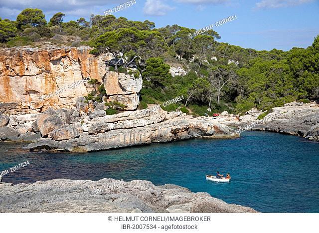 Rowing boat off the rocky coast near Cala de S'Almonia, Cap de ses Salines nature reserve, Cala Llombards, Majorca, Balearic islands, Spain, Mediterranean Sea